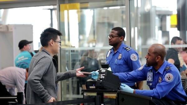 A traveler, left, hands his documents to a Transportation Security Administration officer as part of security screening at John F. Kennedy International Airport. - Sputnik International