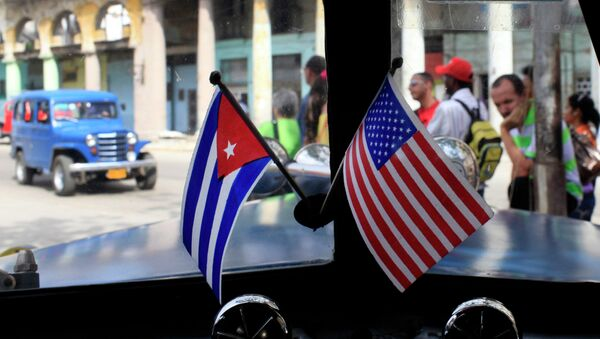 Miniature flags representing Cuba and the United States are displayed on the dash of an American classic car in Havana, Cuba. - Sputnik International