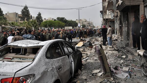 Syrian residents and security forces inspect the damage following a car bomb explosion on April 10, 2015, in the government-controlled majority Alawite neighbourhood of Hay al-Arman, located on the outskirts of the Zahraa district in Homs city - Sputnik International