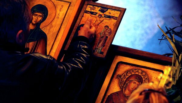 A man touches an icon with the crucifixion of Jesus Christ on Good Friday at St. Petka Orthodox church in Skopje, Macedonia - Sputnik International