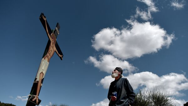 A monk of the Greek Orthodox Church looks at an image of Jesus crucified during the ceremony marking the Apokathelosis, the removal of Christ's dead body from the Cross, which forms a key part of Orthodox Easter, in a ceremony at the Church of the Dormition of the Virgin in Penteli, north Athens - Sputnik International