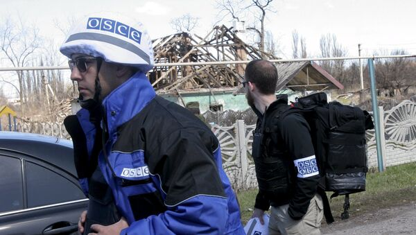 Members of the Special Monitoring Mission of the Organization for Security and Cooperation (OSCE) to Ukraine walk past a house damaged by shelling, in the village of Spartak outside Donetsk April 10, 2015 - Sputnik International