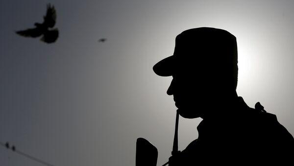 An Afghan policeman stands guard - Sputnik International