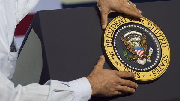 An aide places the Presidential seal on the podium prior to US President Barack Obama speaking during a campaign event at Kissimmee Civic Center in Kissimmee, Florida - Sputnik International