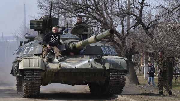 Members of the Ukrainian armed forces drive a tank in the settlement of Luhanske, Donetsk region, March 27, 2015 - Sputnik International