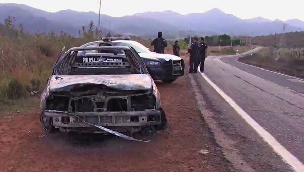 Grab taken from a video of policemen inspecting a burnt police vehicle on April 7, 2015 on a Jalisco state road, Mexico, where at least 15 police officers were killed, overnight, in an ambush carried out by a gang called Jalisco New Generation Drug Cartel.  - Sputnik International