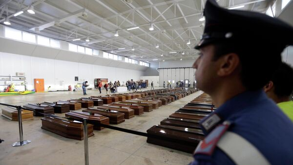 An Italian Carabiniere, paramilitary police man, stands near the coffins of died immigrants inside a hangar of Lampedusa's airport, Italy. - Sputnik International