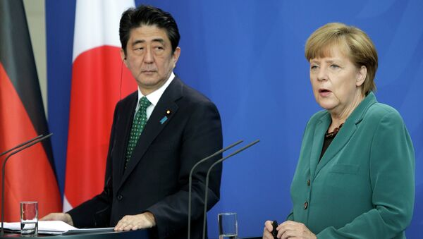 German Chancellor Angela Merkel and Prime Minister of Japan Shinzo Abe address the media during a joint press conference as part of a meeting at the chancellery in Berlin. - Sputnik International