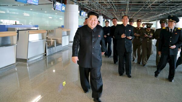 North Korean leader Kim Jong Un (front) smiles as he gives field guidance at the construction site of Terminal 2 of Pyongyang International Airport - Sputnik International