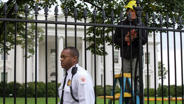 A Secret Service police officer walks outside the White House in Washington, Thursday, Oct. 23, 2014, as a maintenance worker performs fence repairs as part of a previous fence restoration project. - Sputnik International