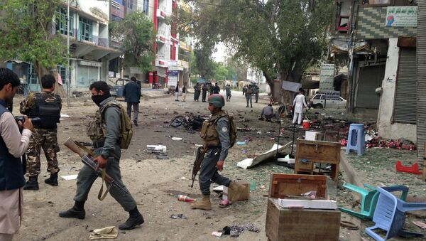 Afghan security forces members inspect the site of a suicide attack near a new Kabul Bank in Jalalabad, east of Kabul, Afghanistan, Saturday, April, 18, 2015. - Sputnik International
