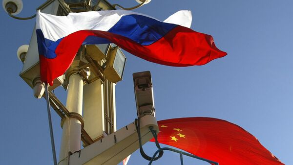 A worker places the Russian and Chinese flags outside Tiananmen Gate - Sputnik International