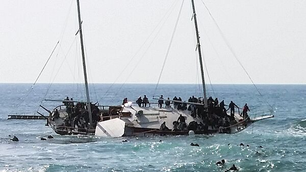 Migrants, who are trying to reach Greece, are seen onboard a capsized sailboat, as others are seen in the water trying to reach the coast of the southeastern island of Rhodes April 20, 2015 - Sputnik International