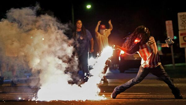 This August 13, 2014, photo by St. Louis Post Dispatch photographer Robert Cohen shows Edward Crawford returning a tear gas canister fired by police who were trying to disperse protesters in Ferguson, Missouri - Sputnik International