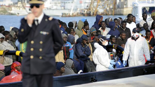 Migrants wait to disembark from a tug boat in the Sicilian harbour of Trapani, April 17, 2015 - Sputnik International