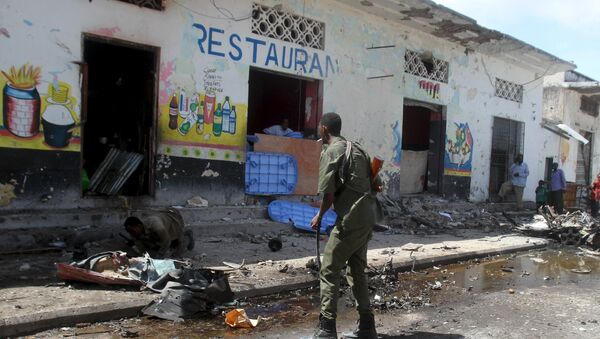 Soldiers inspect the scene of a suicide bomb attack targeting a lunch time crowd at a restaurant in Somalia's capital Mogadishu April 21, 2015 - Sputnik International