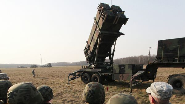 Polish and US soldiers look at a missile defense battery during joint exercises. - Sputnik International