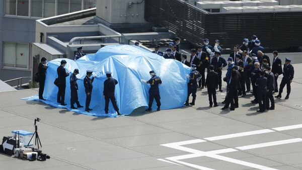 Police and security officials stand around a tarpaulin covering a drone on the roof of Prime Minister Shinzo Abe's official residence in Tokyo April 22, 2015 - Sputnik International