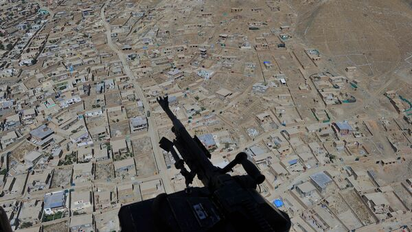Residential houses and a mounted machine gun manned by an Afghan National Army soldier is pictured during a helicopter flight  - Sputnik International