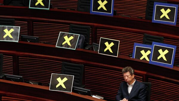 Pro-democracy lawmaker Ronny Tong sits with placards of yellow crosses placed  - Sputnik International