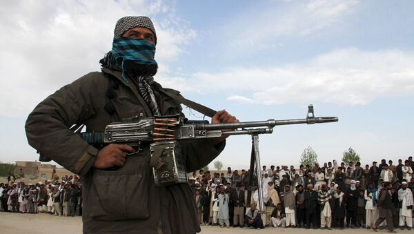 A member of the Taliban insurgent and other people stand at the site during the execution of three men in Ghazni Province on April 18, 2015. - Sputnik International