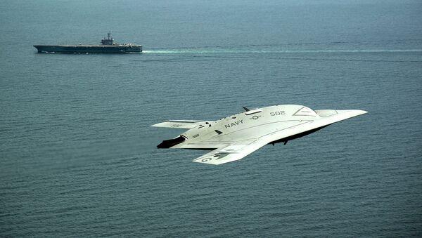 An X-47B Unmanned Combat Air System (UCAS) demonstrator flies near the aircraft carrier USS George H.W. Bush. - Sputnik International