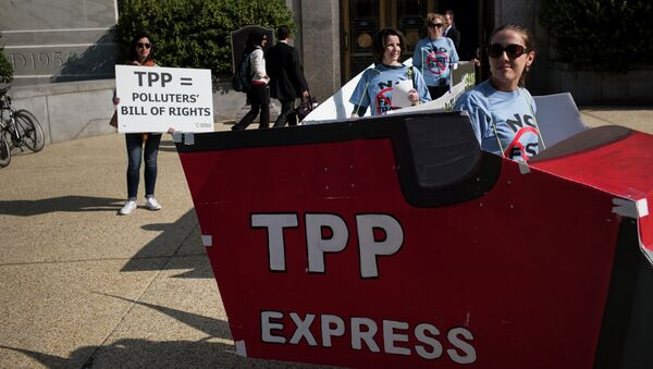 People protesting the TPP look at other protesters, as they rally to advocate for an increase in pay to $15 USD per hour, as part of a Fight for $15 labor effort on Capitol Hill April 22, 2015 in Washington - Sputnik International