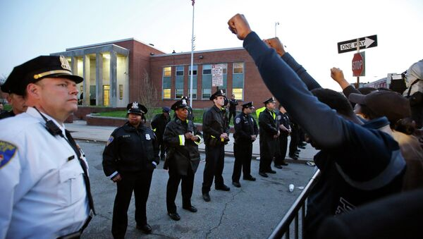 Marchers raise their fists in front of Baltimore police guarding the department's Western District police station during a march for Freddie Gray, Wednesday, April 22, 2015, in Baltimore - Sputnik International