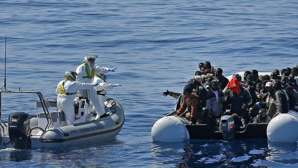 Migrants crowd and inflatable dinghy as rescue vassel  Denaro  (not in picture) of the Italian Coast Guard approaches them, off the Libyan coast, in the Mediterranean Sea - Sputnik International