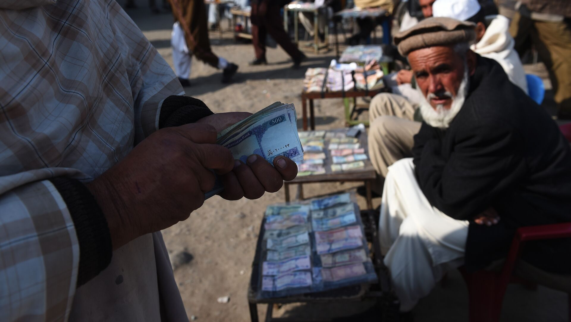 In this photograph taken on December 29, 2014, an Afghan customer (L) counts his Afghani currency notes at a currency exchange market along the roadside in Kabul - Sputnik International, 1920, 16.08.2021