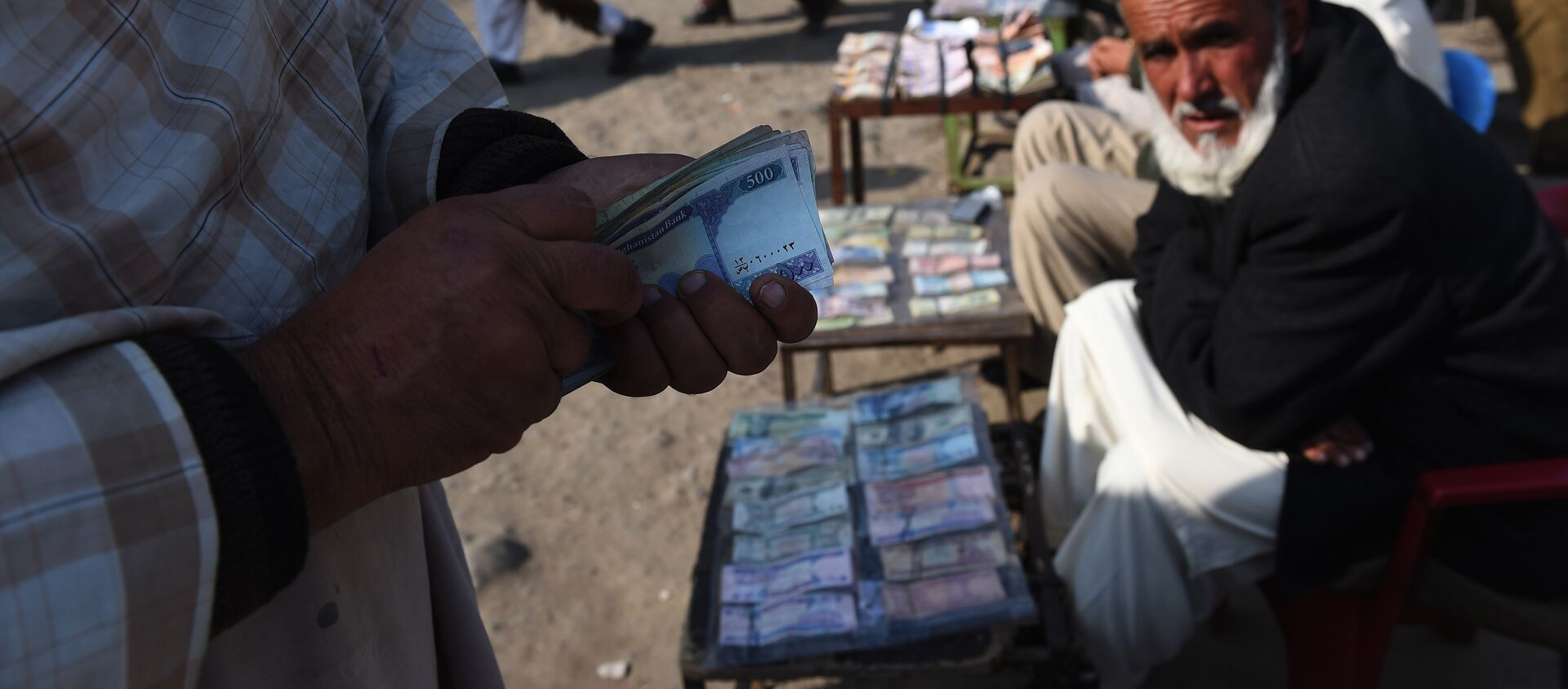 In this photograph taken on December 29, 2014, an Afghan customer (L) counts his Afghani currency notes at a currency exchange market along the roadside in Kabul - Sputnik International, 1920