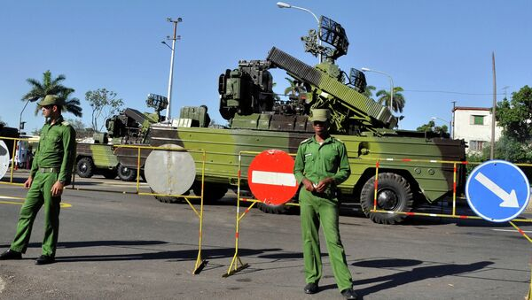 Cuban soldiers guard military vehicles, during a parade rehearsal at Revolution Square in Havana - Sputnik International