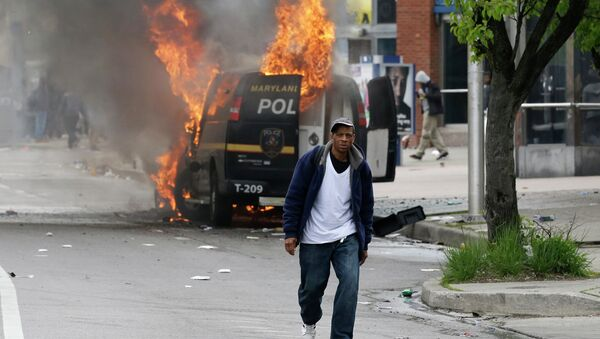 A man walks past a burning police vehicle, Monday, April 27, 2015, during unrest following the funeral of Freddie Gray in Baltimore. Gray died from spinal injuries about a week after he was arrested and transported in a Baltimore Police Department van. - Sputnik International