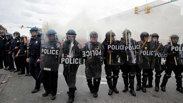 Police advance toward protestors as a store burns, Monday, April 27, 2015, during unrest following the funeral of Freddie Gray in Baltimore. - Sputnik International