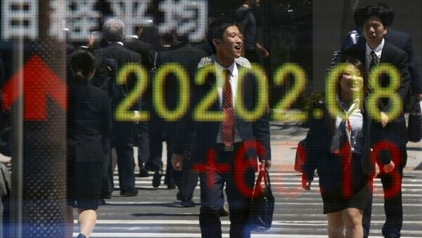 People are reflected in an electronic board displaying Japan's Nikkei share average outside a brokerage in Tokyo April 23, 2015 - Sputnik International