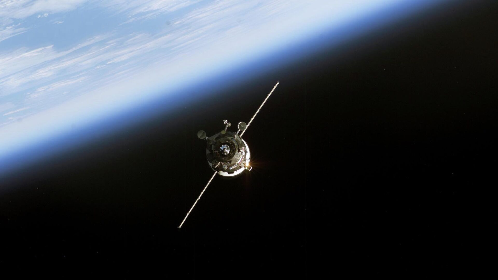 In this 11 June, 2003 NASA image an unmanned Progress supply vehicle (L), backdropped by the blackness of space and Earth's horizon, approaches the Pirs Docking Compartment (out of frame) attached to the Zvezda Service Module on the International Space Station (ISS) - Sputnik International, 1920, 26.07.2021