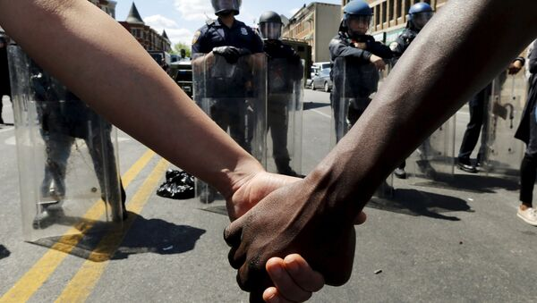 Members of the community hold hands in front of police officers in riot gear outside a recently looted and burned CVS store in Baltimore, Maryland, United States April 28, 2015 - Sputnik International