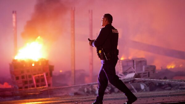A police officer walks by a blaze, Monday, April 27, 2015, after rioters plunged part of Baltimore into chaos, torching a pharmacy, setting police cars ablaze and throwing bricks at officers - Sputnik International