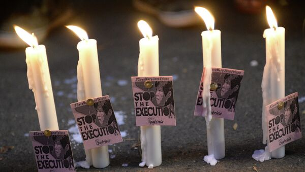 Candles and portraits of Filipina Mary Jane Veloso, who is due for execution in Indonesia, are seen during the vigil in front of the Indonesian embassy in Manila on April 27, 2015. - Sputnik International