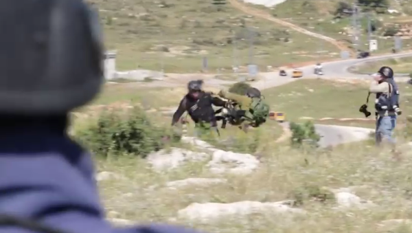 In this video screenshot, an Israeli soldier can be seen pushing a photojournalist. - Sputnik International