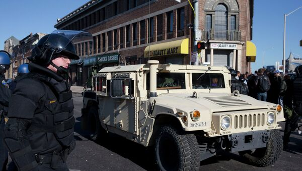 A National Guard vehicle drives by a Maryland State Trooper Tuesday, April 28, 2015, in the aftermath of rioting following Monday's funeral for Freddie Gray. - Sputnik International