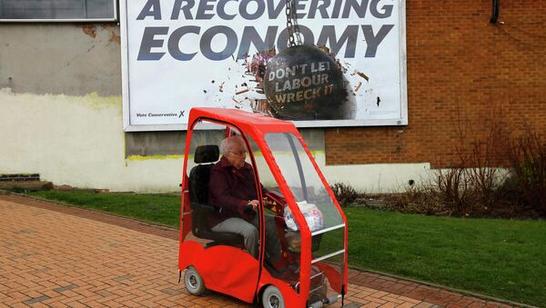 A woman drives a mobility scooter past a Conservative Party billboard in Bedworth, central England, April 1, 2015 - Sputnik International