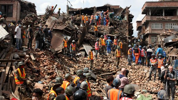 People watch as rescuers search for bodies at the site of a building which collapsed during an earthquake in Bhaktapur near of Kathmandu, Nepal in this Red Cross handout picture taken on April 29, 2015 - Sputnik International