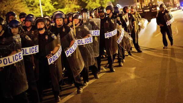 Police in riot gear line up near the scene of Monday's riots ahead of a 10 p.m. curfew Wednesday, April 29, 2015, in Baltimore. The curfew was imposed after unrest in Baltimore over the death of Freddie Gray while in police custody. - Sputnik International
