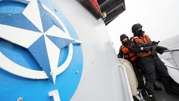 Two Norwegian sailors onboard the Norwegian support vessel Valkyrien pose for photographers next to the NATO logo - Sputnik International