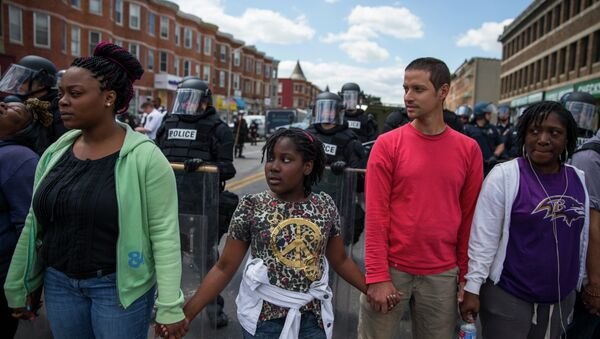 From left, Adrienne Horton, 11 year-old Shenya Milford, Vinny Bevivino, and Lakia McDaniel, all from Baltimore, Md., gather to sing Amazing Grace during a gathering of demonstrators after an evening of riots following the funeral of Freddie Gray on Tuesday, April 28, 2015, in Baltimore - Sputnik International