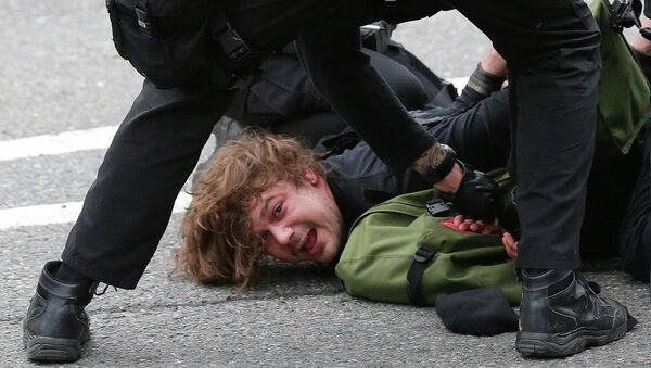 Police officers arrest a man during a May Day anti-capitalism march, Friday, May 1, 2015 in Seattle. - Sputnik International