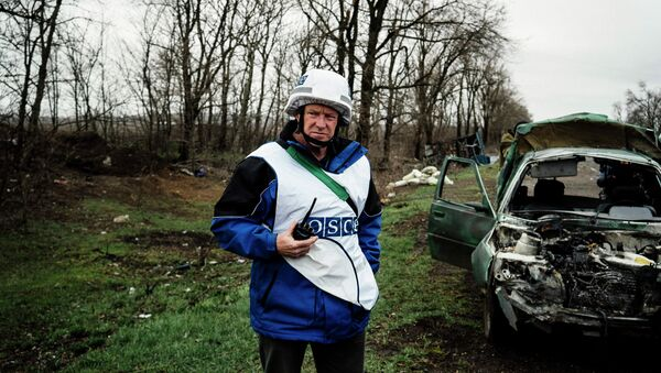 An International observer of the Organization for Security and Co-operation in Europe (OSCE) stands next to a destroyed car after shelling during an inspection tour near the village of Shirokino, near the eastern Ukrainian port city of Mariupol - Sputnik International