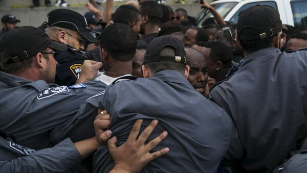 Israeli policemen push protesters, mainly whom are Israeli Jews of Ethiopian origin, during a demonstration against what they say is police racism and brutality, after the emergence last week of a video clip that showed policemen shoving and punching a black soldier during a protest in Tel Aviv May 3, 2015. - Sputnik International