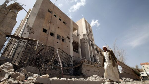 A man looks at a school destroyed by an air strike as he flees his home in Sanaa April 28, 2015 - Sputnik International